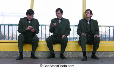 three businessmen clones sit near window - Three businessmen...