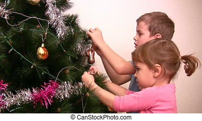 children hangs up fur-tree toy on christmas tree - Children...