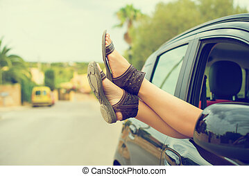 Woman's legs out of the car window. Vintage effect photo.
