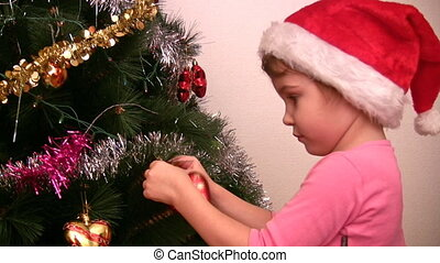 little girl hangs up fur-tree toy on christmas tree - Little...