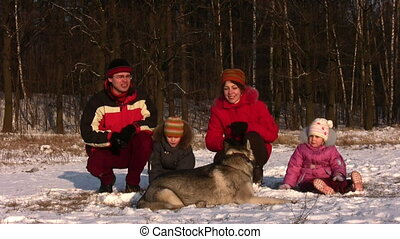 family of four playing in winter park and dog