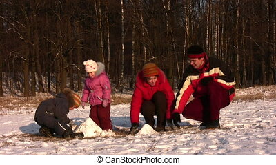 family of four playing in winter park