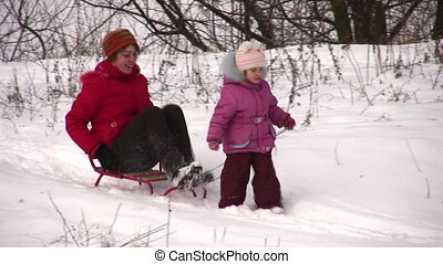 little girl with mother on sled