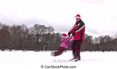 father rotating little girl in christmas hats - Father...