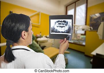Dentist checking x-ray at dental clinic