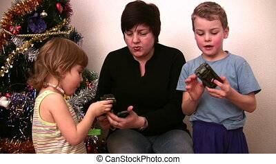 Woman with children consider toys near christmas tree