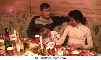 Family with small girl sit for festive table
