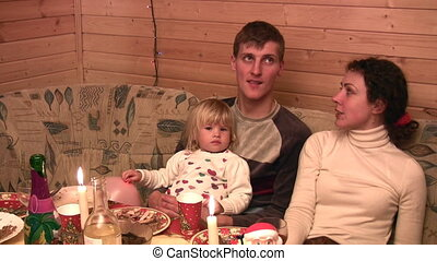 Family with small girl speaking at festive table