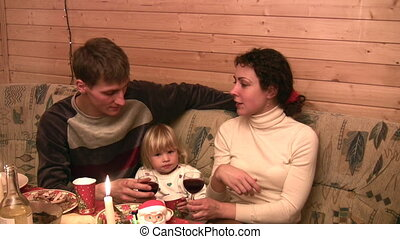 Family with child at table with wine