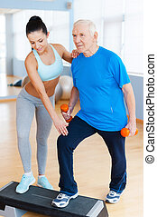 You can do it! Full length of confident female physical therapist working with senior man in health club