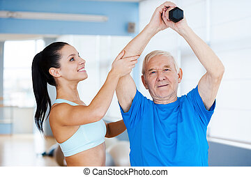 You are making great progress! Confident female physical therapist working with senior man in health club
