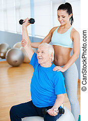 Just a little higher! Confident female physical therapist working with senior man in health club