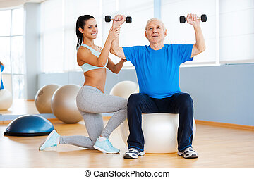 Weight exercises. Confident female physical therapist working with senior man in health club