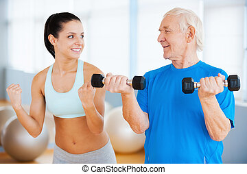 And three times more. Confident female physical therapist showing how to make weight exercise to senior man in health club