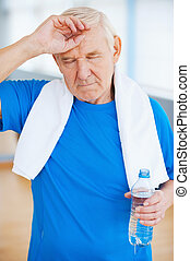 Feeling tired after sports training. Tired senior man with towel on shoulders keeping eyes closed and touching forehead while standing in health club