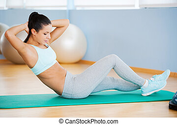 Training her abs. Beautiful young woman in sports clothing exercising while lying on exercise mat