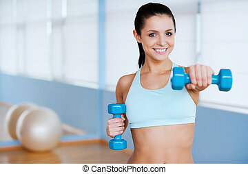 Exercising with dumbbells. Beautiful young woman in sports clothing exercising with dumbbells and smiling while standing in health club