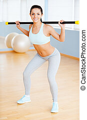 Keeping her body fit. Beautiful young woman in sports clothing exercising and smiling while standing in health club