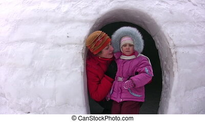 Mother with small girl looks from snow building