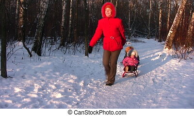 Mother with children on sled