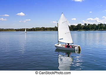 White boat sailing - Small white boat sailing on the lake on...