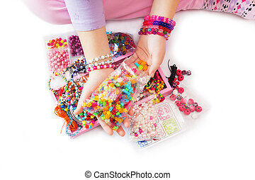 Colorful Beads - Young Girl's Hand with Many Different Beads...