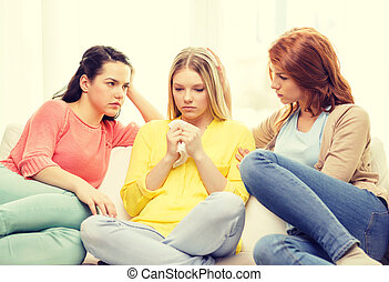 two teenage girls comforting another after breakup -...