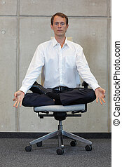 meditating businessman in lotus pos - meditating caucasian...