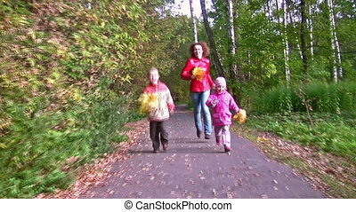 mother with children running in autumn park