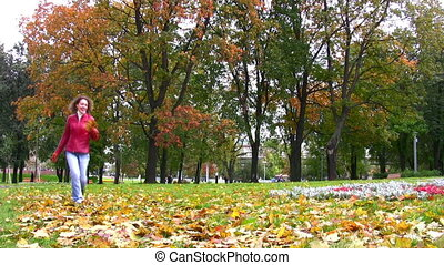 woman in autumn park throwing leaves - Woman throwing leaves...