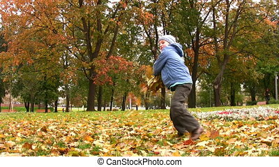 child throws autumn leaves