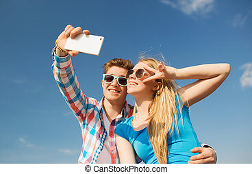 smiling couple with smartphone making selfie - summer,...