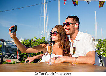 smiling couple drinking champagne at cafe - love, dating,...