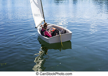 Young Girl sails on the lake on a beautiful sunny day