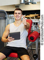 smiling young man with tablet pc computer in gym