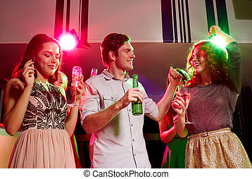 smiling friends with wine glasses and beer in club - party,...