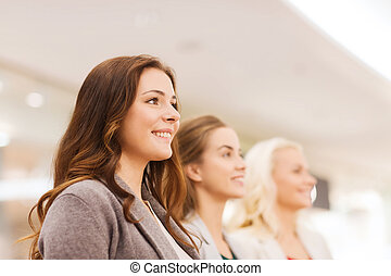 happy young women in mall or business center - sale,...