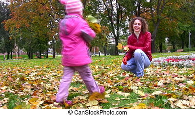 mother with little girl throw autumn leaves