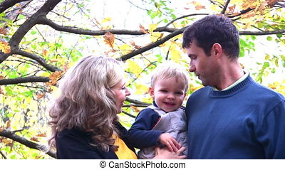 parents look at boy in park. faces - Faces of parents which...