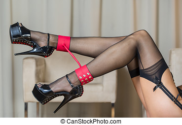 Legs with stockings, garter belt, ankle cuffs and high heels...