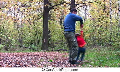 father rotating girl in autumn wood