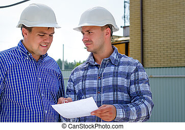 Two builders or engineers discussing paperwork - Two...