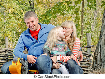 Happy young family relaxing outdoors with the father sitting...