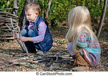 Two young children playing with sticks outdoors - Two young...