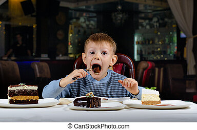 Little boy cannot believe his luck as he sits at the dining...