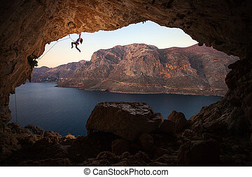 Silhouette of female rock climber on cliff in cave -...