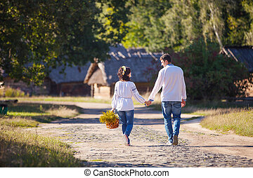 Young couple walking along the road - Young couple in...