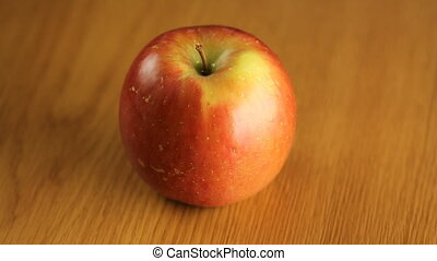 Red Apple rotating on wood - Fresh organic red apple...