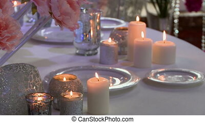 Lighted candles on wedding table, close-up