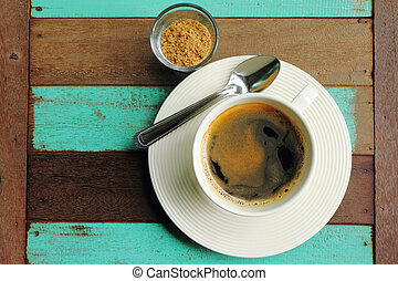 Top view of a black coffee in white cup with sugar on old wood.